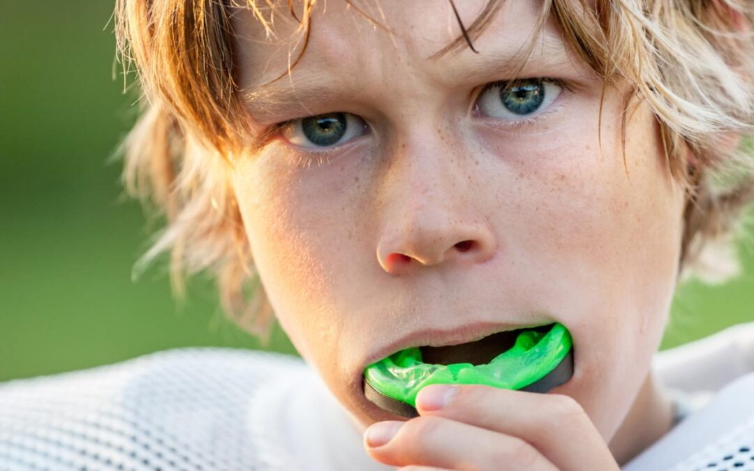 child with a mouthguard in his mouth for sports